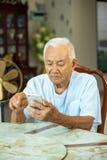 在家使用手机的老人 免版税库存图片