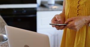 在家使用手机的资深妇女在厨房4k 影视素材