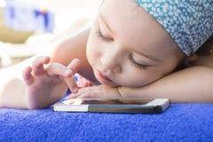 在家使用手机的逗人喜爱的小女孩 免版税库存图片