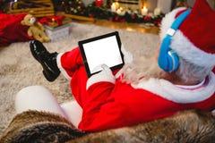 在家使用数字式片剂的圣诞老人 免版税库存照片