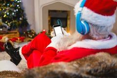 在家使用数字式片剂的圣诞老人 库存照片