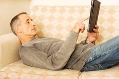 在家使用数字式片剂的成熟人 免版税库存图片