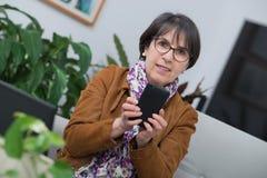 在家使用智能手机的中年深色的妇女 免版税库存照片