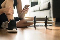 在家使用智能手机的人在锻炼期间 免版税库存照片