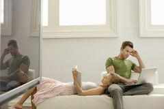 在家使用有妇女阅读书的人膝上型计算机 库存图片