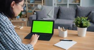 在家使用有绿色大模型屏幕的年轻女人膝上型计算机在桌 影视素材