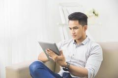 在家使用片剂个人计算机的亚裔年轻人 免版税库存照片