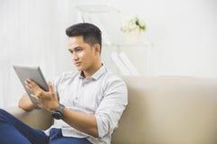 在家使用片剂个人计算机的亚裔年轻人 免版税图库摄影