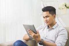 在家使用片剂个人计算机的亚裔年轻人 图库摄影