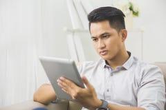 在家使用片剂个人计算机的亚裔年轻人 免版税库存图片