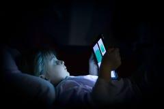 在家使用片剂技术的小孩女孩在床在夜之前 卧室观看的严肃或toughtful孩子女儿 免版税库存照片