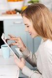 在家使用片剂计算机的少妇 免版税库存图片
