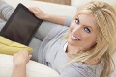 在家使用片剂计算机的美丽的妇女 库存图片