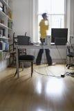 在家使用电话办公室的被弄脏的人 库存照片