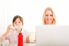 在家使用的母亲和的女儿 免版税库存图片