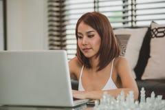 在家使用膝上型计算机的可爱的亚裔妇女 免版税库存照片