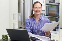在家使用膝上型计算机的女性自由职业者的工作者在厨房 免版税图库摄影