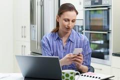 在家使用膝上型计算机的女性自由职业者的工作者在厨房 免版税库存图片