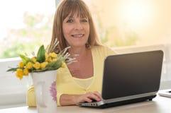 在家使用膝上型计算机的妇女画象,光线影响 免版税库存图片
