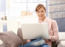 在家使用膝上型计算机的少妇 免版税库存图片