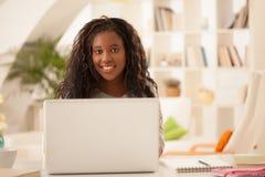 在家使用膝上型计算机的微笑的非洲十几岁的女孩 免版税图库摄影