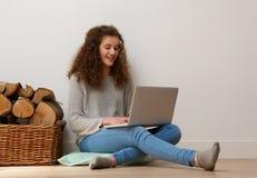 在家使用膝上型计算机的愉快的十几岁的女孩 免版税库存图片