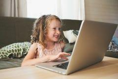 在家使用膝上型计算机的愉快的孩子 学会与计算机和互联网的学校女孩 免版税库存照片