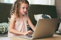 在家使用膝上型计算机的愉快的孩子 学会与计算机和互联网的学校女孩 免版税图库摄影