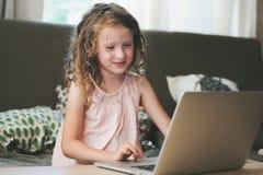 在家使用膝上型计算机的愉快的孩子 学会与计算机和互联网的学校女孩 库存图片