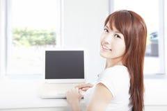 在家使用膝上型计算机的愉快的少妇 免版税库存图片