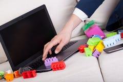 在家使用膝上型计算机的繁忙的父亲 免版税库存照片