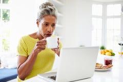 在家使用膝上型计算机的非裔美国人的妇女在厨房 图库摄影