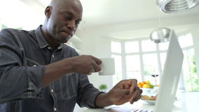 在家使用膝上型计算机的非裔美国人的妇女在厨房 影视素材