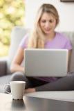 在家使用膝上型计算机的年轻美丽的妇女 图库摄影