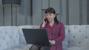 在家使用膝上型计算机,在沙发的电话的严肃的妇女 影视素材