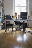 在家使用计算机的人 免版税库存图片