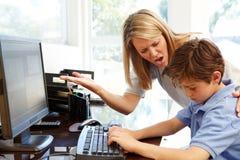 在家使用计算机的母亲和儿子 库存照片