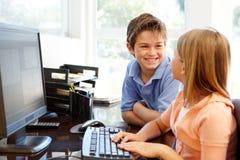 在家使用计算机的年轻男孩和女孩 免版税图库摄影