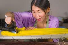在家使用铁厨房电烙的衣裳的年轻俏丽和愉快的亚裔韩国妇女微笑快乐和无忧无虑享用domest 库存照片