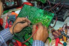 在家修理和检查老电视主板与多用电表在桌上 免版税库存图片