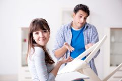 在家修理打破的椅子的妻子帮助的丈夫 库存照片