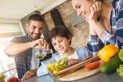 在家倾斜在桌的家庭在一起看愉快父亲的厨房里穿戴与油特写镜头的沙拉 免版税库存图片