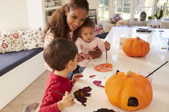 在家做万圣夜装饰的母亲和孩子 免版税库存照片