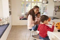 在家做万圣夜装饰的母亲和孩子 免版税图库摄影