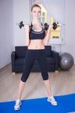 在家做与哑铃的亭亭玉立的妇女锻炼 图库摄影