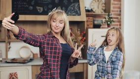 在家做与智能手机照相机的微笑的妈妈和女儿selfie照片在厨房里 家庭、厨师和人概念 股票视频