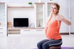 在家做体育锻炼的孕妇 免版税库存照片