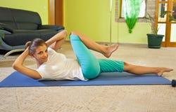 在家做健身的愉快的少妇。 免版税库存照片
