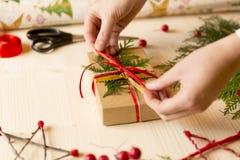 在家做圣诞节礼物的妇女用手在假日前 库存图片