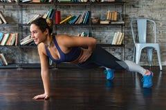 在家做在一条胳膊的年轻健身妇女俯卧撑锻炼在地板上 免版税库存照片